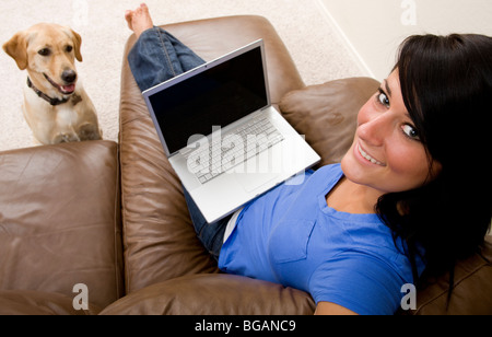 With a pet yellow Labrador at her feet, a young woman relaxes at home with a laptop. - Stock Photo