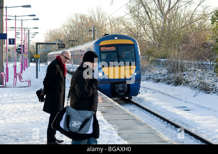 Commuters on a snow covered railway platform as a train comes in..  Photo by Gordon Scammell - Stock Photo