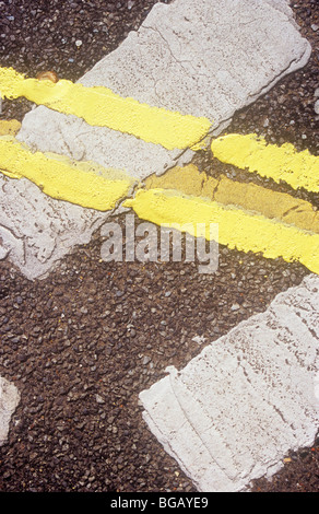 Detail from above of double yellow lines running across white Give Way lines all thickly repainted over old blurred - Stock Photo