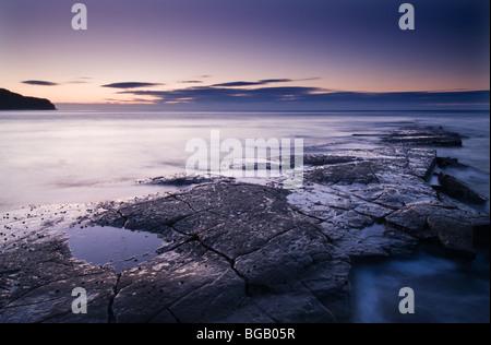 Dawn light over rock ledges at Kimmeridge Bay, Dorset - Stock Photo