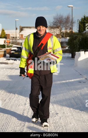 A postman makes his Christmas deliveries despite the snowfall which has affected road conditions in the north of - Stock Photo