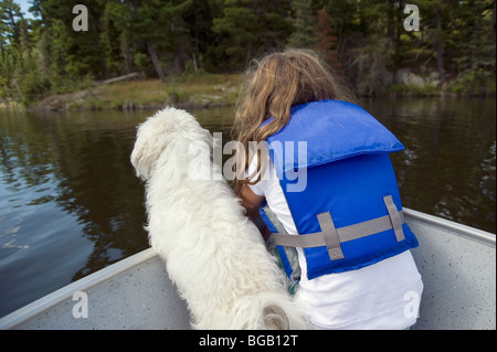 Little girl with little white dog in boat; Lake of the Woods, Lulu, Ontario, Canada - Stock Photo