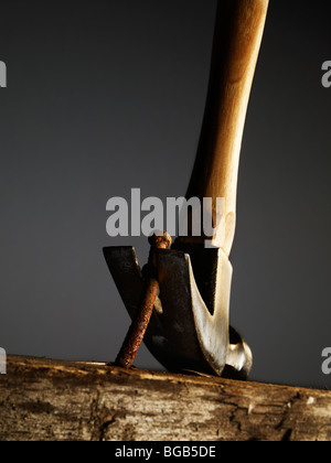 Hammer Removing A Nail From A Old Wooden Surface - Stock Photo