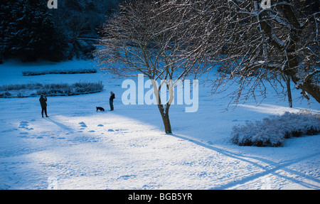 December snow scene Kelso Scottish Borders UK - walking in Bridgend Park man takes photo of woman with dog - Stock Photo
