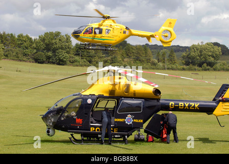 Dorset Police helicopter with air ambulance helicopter hovering - Stock Photo