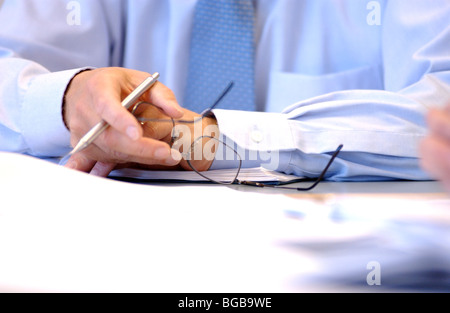 Royalty free photograph of business meeting with papers and hands in focus London UK - Stock Photo