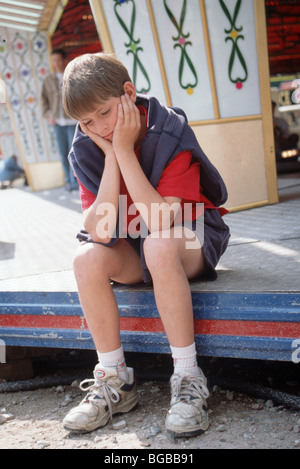 Lonely boy ponder on funfair attraction - Stock Photo