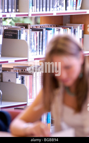 Photograph of girl woman library blur student books revision UK - Stock Photo