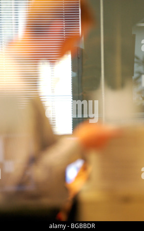 Royalty free photograph of business man in office reflections in glass reading a report - Stock Photo