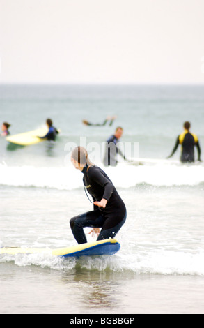 Royalty free photograph of female surfer in the sea on a cold winter day in Cornwall UK - Stock Photo
