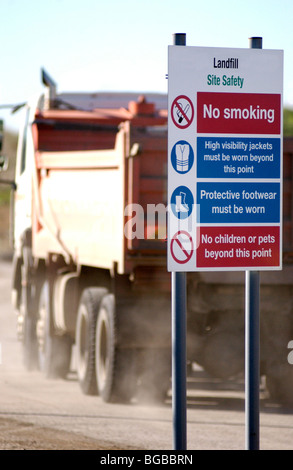 Royalty free photograph showing sign at the entrance to landfill site with dumping truck/lorry driving into the - Stock Photo