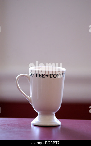 Royalty free photograph of coffee cup on table in business/home office with blurred background for type. - Stock Photo