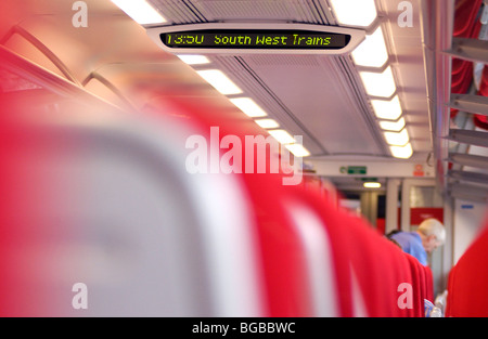 Royalty free photograph of the interior of South West train carriage showing announce display screen with a row - Stock Photo