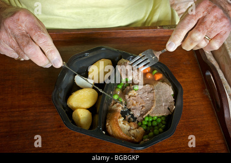 Old age pensioner eating a Birds Eye traditional beef ready meal - Stock Photo