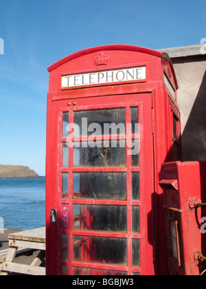 Old fashioned red telephone box and post box at sea front in Pennan, Aberdeenshire, Scotland - Stock Photo