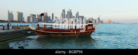 A ferry prepares to leave for an afternoon jaunt round Doha Bay, with Qatar's high-rise skyline in the background. - Stock Photo