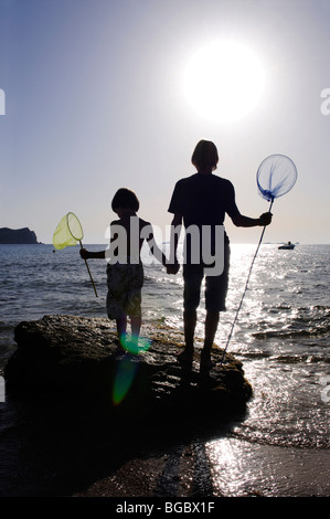 Children fishing with dip nets, Cala Conta, Ibiza, Pine Islands, Balearic Islands, Spain, Europe - Stock Photo