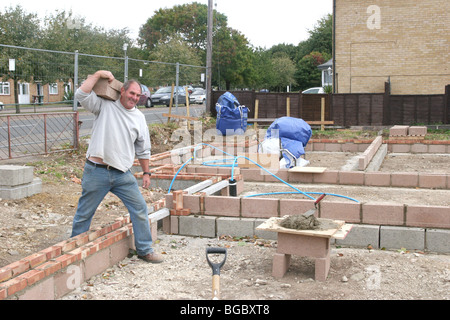 A bricklayer carrying bricks on a building site in the UK. - Stock Photo
