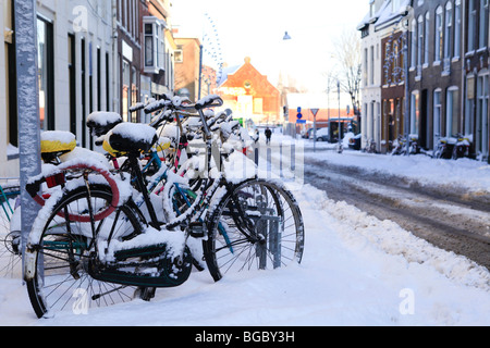 Row of bikes in the snow in Dutch Groningen - Stock Photo