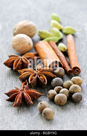 Assorted whole spices close up on wooden background - Stock Photo