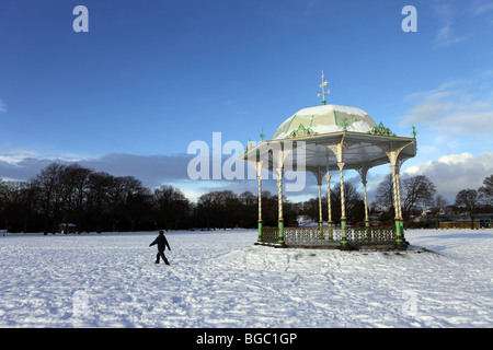 Walker in front of the Victorian traditional bandstand in Duthie Park in Aberdeen, Scotland, UK, seen in the snow - Stock Photo