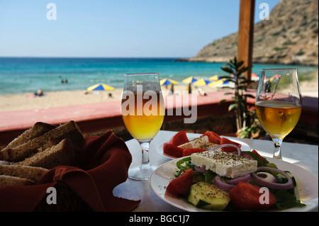 Beer glasses and Greek salad in a tavern, Arkassa, Karpathos, Aegean Islands, Aegean Sea, Greece, Europe - Stock Photo