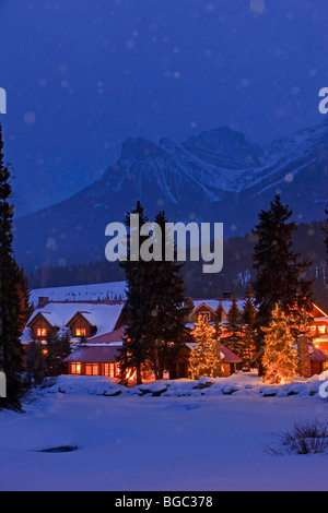 Winter night scene of the Post Hotel located on the snow covered banks of the Pipestone River, Lake Louise, Banff - Stock Photo