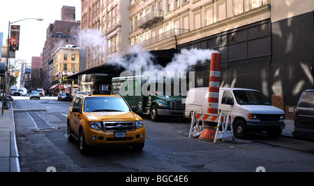 Steam rises from the subway below the streets in Manhattan New York USA - Stock Photo