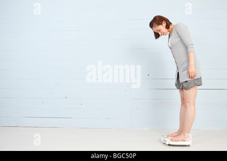 Young woman standing on weight scale - Stock Photo