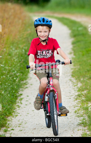 A boy, 7 years, riding a bicycle on a dirt road - Stock Photo