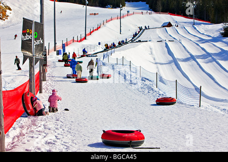 People walking up to the magic carpet lift with their tubes at the Coca-Cola Tube Park on Blackcomb Mountain, Whistler - Stock Photo