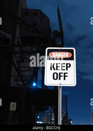 Danger - Keep Off sign with an industrial building in the background - Stock Photo
