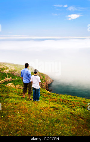 Father and son looking at foggy ocean view in Newfoundland - Stock Photo