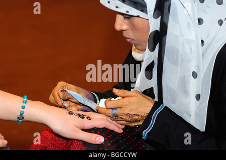 Arab woman applies Henna paste on a hand to draw a Henna tattoo, Yemen - Stock Photo