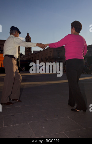 A couple dance in the Plaza de Armas Morelia with a view in the background of Templo de los Agustinos in Morelia - Stock Photo