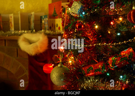 decorated christmas tree on christmas eve night in a living room in the uk - Stock Photo