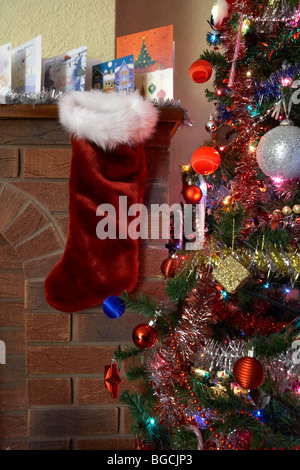 empty christmas stocking hanging below row of christmas cards on a mantlepiece in a christmas decorated living room - Stock Photo