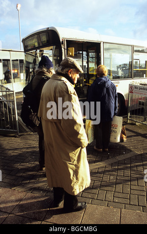 Old Elderly Man Alone In Raincoat And Cap Waiting to Board A Bus At Hanley Bus Station - Stock Photo