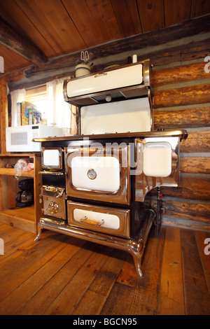 Old stove in the kitchen of a rustic log cabin - Stock Photo