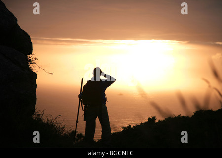 Sunset and girl at Finisterre cape, Camino de Santiago - Stock Photo