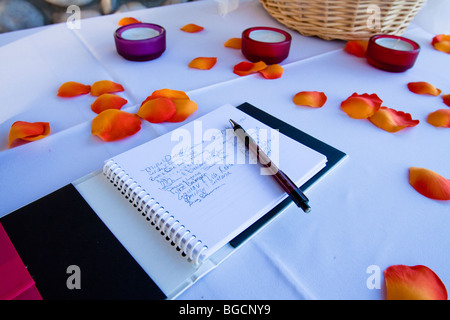 Wedding guest book with signatures on a table with flower petals and votive candles - Stock Photo