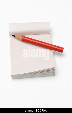 Red short pencil on mini notepad on white background - Stock Photo