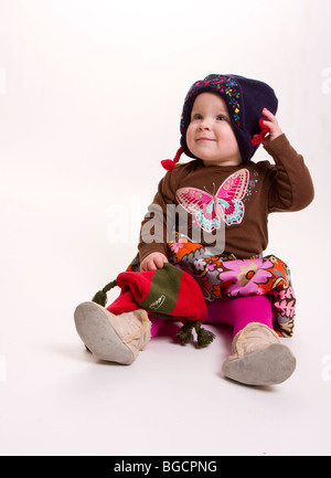 1 year old little girl wearing winter hat isolated on white - Stock Photo