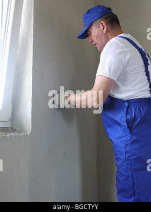 Electrician installing wall socket in newly built house - Stock Photo