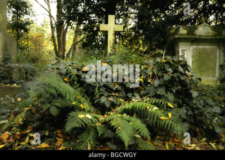 gravestones and undergrowth in Highgate Cemetery in London England UK - Stock Photo