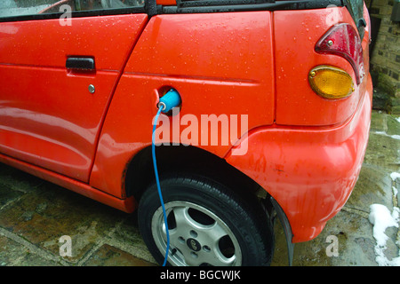 G Wiz GWiz G-Wiz clean green battery electric powered vehicle car plug plugged in charge charging recharging recharge - Stock Photo