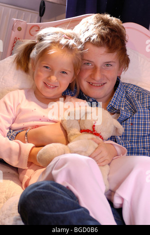 Brother and little sister playing in bed, going to bed, taking to bed, tucking in - Stock Photo