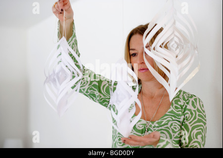 Woman with a wind chime, paper mobile, creativity, artist - Stock Photo