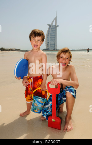 Children playing on the beach in front of the Burj al Arab Hotel, Dubai, United Arab Emirates, Middle East - Stock Photo