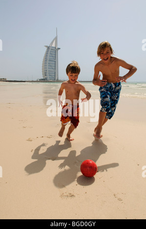 Children playing soccer on the beach in front of the Burj al Arab Hotel, Dubai, United Arab Emirates, Middle East - Stock Photo